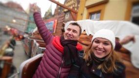 Par som skrattar och har gyckel i den ganska julen Vänner under vinterferie i karusellen eller karusell på stock video