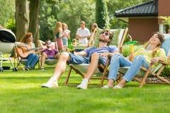 Par som solbadar i trädgården royaltyfria bilder