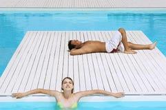 Par som solbadar på poolsiden Arkivbild