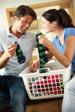 Par som sorterar tvätterit i kök royaltyfri foto
