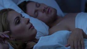 Par som sover i säng, missnöjd fru som väckas av den höga snarkningen av maken stock video