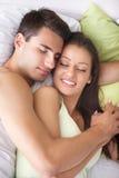 Par som sover och kramar på sängen Royaltyfri Foto