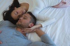 Par som sover på säng i sovrum royaltyfri bild