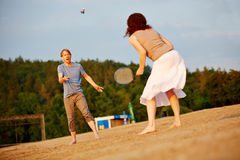 Par som spelar badminton på stranden Royaltyfri Foto