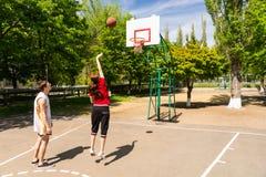 Par som spelar basket på den utomhus- domstolen Arkivbild