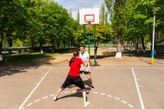 Par som spelar basket på den utomhus- domstolen Arkivfoto
