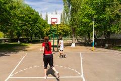 Par som spelar basket på den utomhus- domstolen Royaltyfri Foto