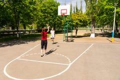 Par som spelar basket på den utomhus- domstolen Arkivbilder
