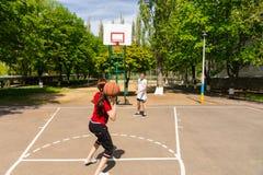 Par som spelar basket på den utomhus- domstolen Royaltyfri Fotografi