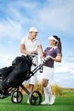 Par som spelar golf på en solig dag Royaltyfri Foto