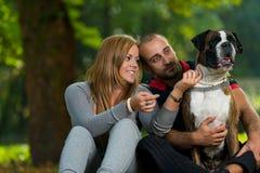 Par som spelar med hunden arkivfoto