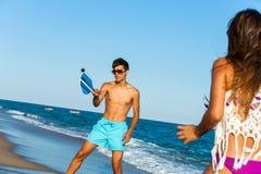 Par som spelar strandtennis. Arkivfoto