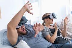 Par som spelar videogames i VR-exponeringsglas arkivfoto