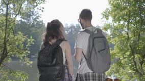 Par som står på flodstranden i skogen med att peka för ryggsäckar som är bort Ung fotvandra för man och för kvinna Begrepp av lager videofilmer