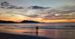 Par som står under solnedgång arkivfoton