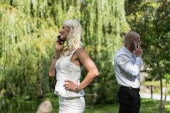 Par som talar på mobil eller, ilar telefonen Mannen och kvinnan talar med telefonen Ungdomaranvänder mobiltelefonen för appell pa Arkivfoton