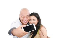Par som tar deras bild på en mobil telefon Arkivfoto