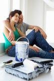 Par som tar ett avbrott från att dekorera huset Royaltyfria Bilder