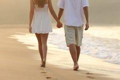 Par som tar ett gåinnehav händer på stranden Arkivbild