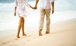 Par som tar ett gåinnehav händer på stranden Arkivfoto