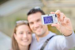 Par som tar fotoet själva med den digitala kameran Fotografering för Bildbyråer