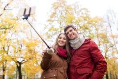 Par som tar selfie vid smartphonen i höst, parkerar arkivfoto