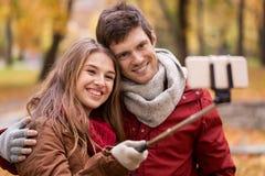 Par som tar selfie vid smartphonen i höst, parkerar royaltyfria bilder