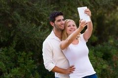 Par som tar selfiefotoet med den digitala minnestavlan Arkivfoto