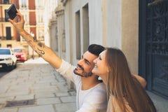 Par som tar självståenden med iphone härligt parbarn Royaltyfri Bild