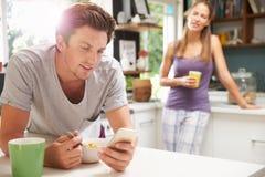 Par som äter frukoststunden som kontrollerar mobiltelefonen Fotografering för Bildbyråer