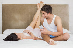 Par som till varandra talar, medan koppla av på säng Royaltyfri Fotografi
