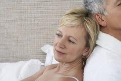 Par som tillbaka sitter för att dra tillbaka i sovrum Royaltyfria Bilder