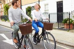 Par som tillsammans cyklar längs den stads- gatan Royaltyfria Bilder