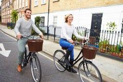 Par som tillsammans cyklar längs den stads- gatan Fotografering för Bildbyråer