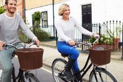 Par som tillsammans cyklar längs den stads- gatan Royaltyfria Foton
