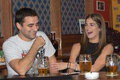 Par som tillsammans dricker och har gyckel arkivfoto