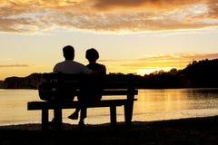 Par som tillsammans håller ögonen på en härlig solnedgång arkivbilder