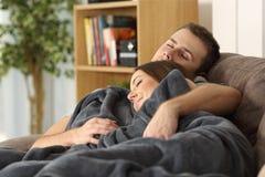 Par som tillsammans hemma sover på en soffa fotografering för bildbyråer
