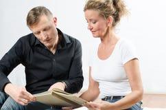 Par som tillsammans läser i en bok Royaltyfri Fotografi