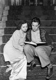 Par som tillsammans läser på trappa (alla visade personer inte är längre uppehälle, och inget gods finns Leverantörgarantier som  Arkivbild