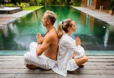 Par som tillsammans mediterar och sitter i lotusblomma, poserar arkivbild