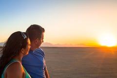 Par som tillsammans ser på solnedgången Royaltyfria Bilder