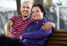 Par som tillsammans sitter på bänk Fotografering för Bildbyråer