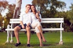 Par som tillsammans sitter på, parkerar bänkhöst royaltyfria foton