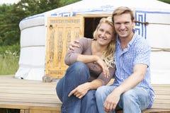 Par som tycker om campa ferie i traditionella Yurt Royaltyfri Foto