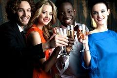 Par som tycker om champagne eller vin på ett parti Royaltyfri Foto