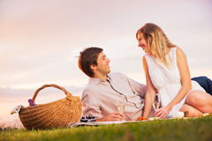 Par som tycker om den romantiska solnedgångpicknicken Royaltyfria Foton
