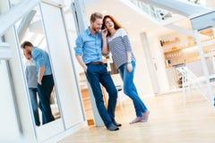 Par som tycker om deras moderna nya lägenhet Arkivbild