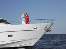 Par som tycker om drinkar på yachten royaltyfri bild