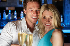Par som tycker om exponeringsglas av Champagne In Bar Royaltyfri Foto